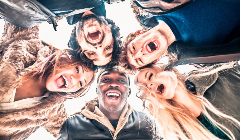 Multi-ethnic group of friends in circle - Several people of diverse ethnics smiling and looking down at camera - Concepts about friendship, teamwork, immigration and unity