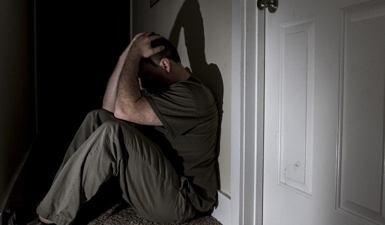 man sad holding his head in his hands. in a darkened hallway