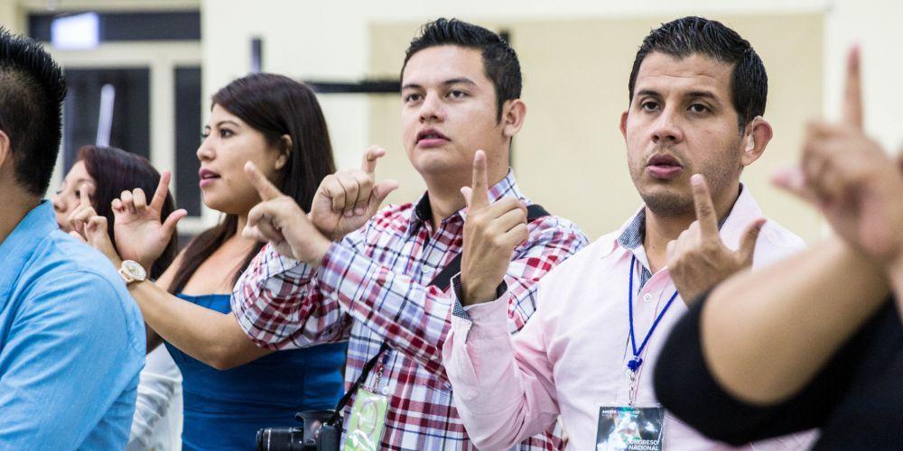 Participantes cantam na linguagem de sinais durante conferência