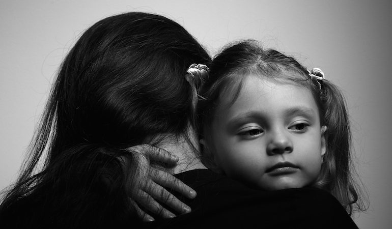Family lifestyle. Daughter hugging her mother and looking serious. Black and white portrait