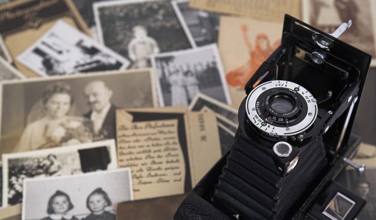 Nostalgische Rollfilmkamera ,im Hintergrund alte Familienfotos