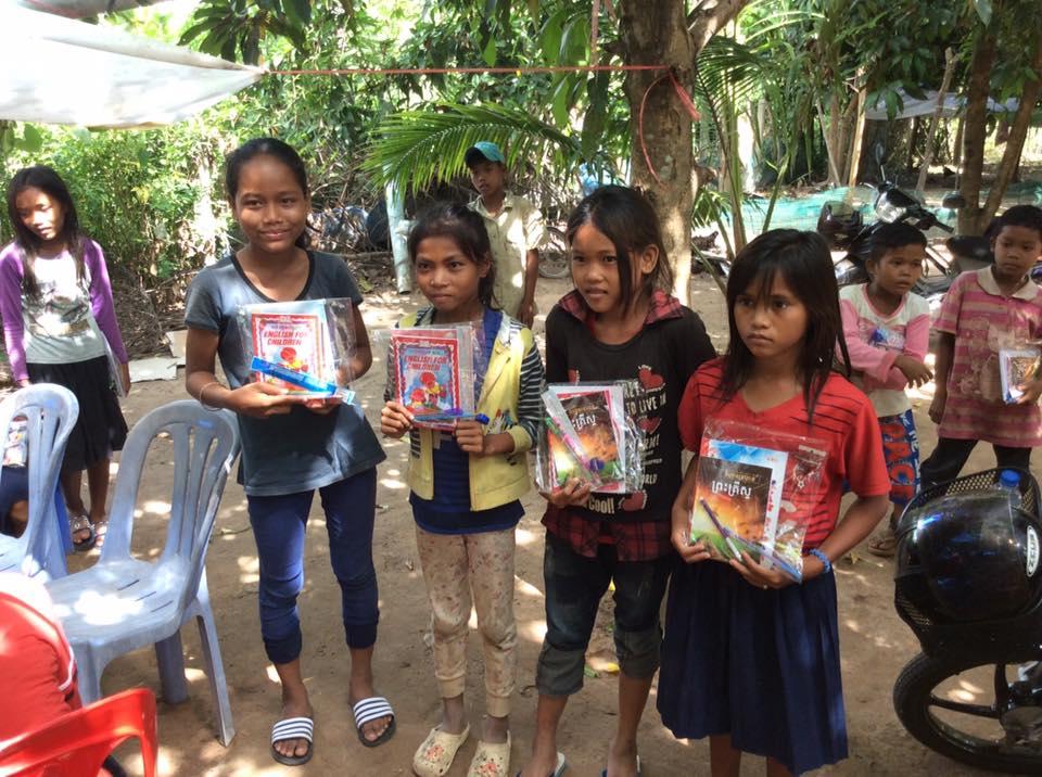 Groupe d'enfants ayant reçu du matériel scolaire et des livres chrétiens