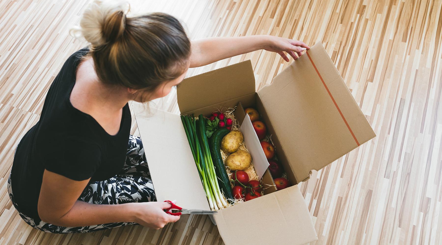 Frau öffnet Kiste mit Lebensmitteln, Lieferservice per postsendung